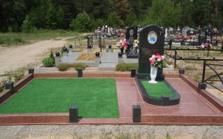 Гранитный памятник черного цвета, благоустроен газоном и оградой из гранита